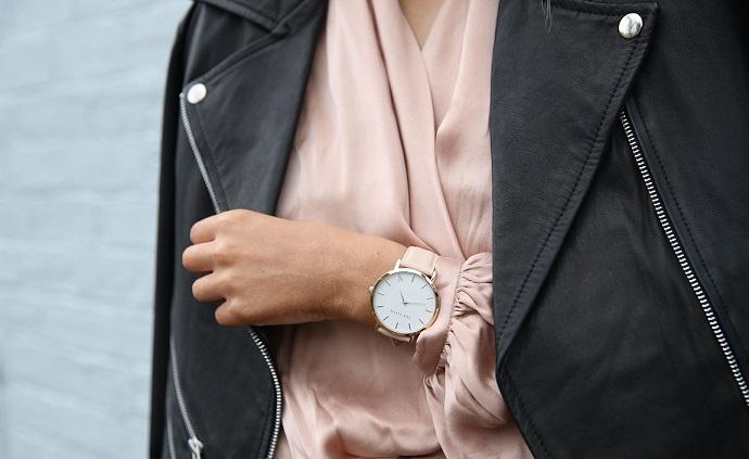 Gros plan d'un top en satin rose poudré porté sous un perfecto en cuir